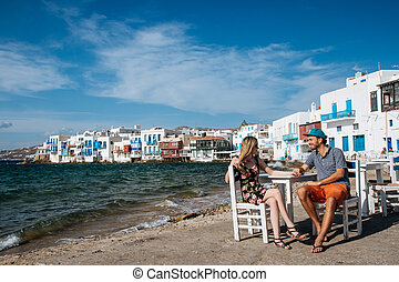 Couple sitting on chairs at the beach, holding hands - Young...