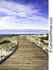 Boardwalk over sand dunes with blue sky and clouds in...