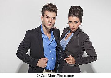 Beautiful fashion woman pulling her boyfrineds jacket while...