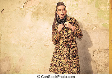 Gorgeous fashion woman fixing her coat while looking away...