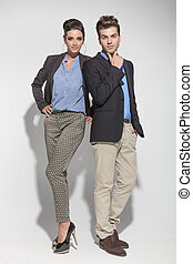 fashion couple posing on light grey background - Full lenght...
