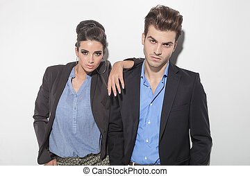 Casual couple leaning on a light grey wall