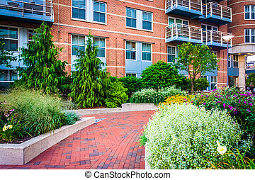 Garden and building along a walkway at Battery Wharf in...