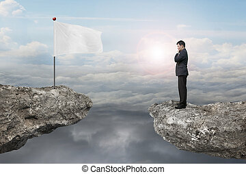 Manager standing on cliff with blank flag and sunlight...