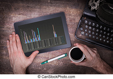 Tablet touch computer gadget on wooden table, graph, vintage...