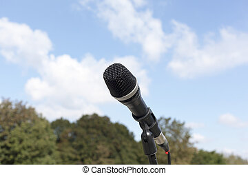 Microphone in focus against blurred trees and sky