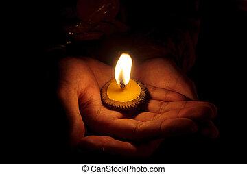 Candle and hand - candle burning in hands in the dark