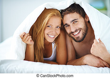 Happy family life - Portrait of young couple under the sheet