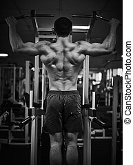Strengthening muscles - Young man training on special sport...