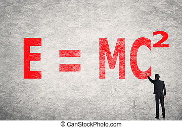 text on wall, E = mc2 - Asian businessman write text on...