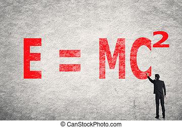 text on wall, E = mc2 - Asian businessman write text on...