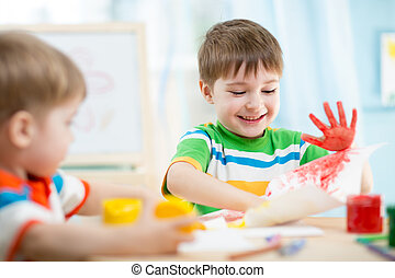 smiling kids playing and painting at home or kindergarten or...