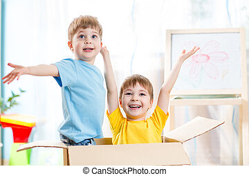 happy kids boys playing and sitting in cardboard box - two...