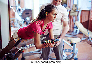 Sport activity - Sportive girl training in gym with her...