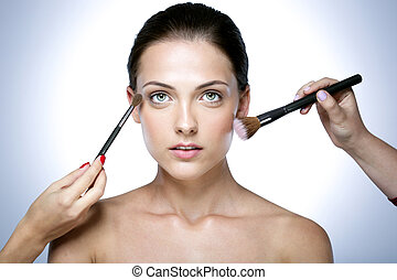 Closeup portrait of a woman applying dry cosmetic tonal...
