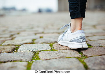 Leg of female jogger walking on pavement. Focus of shoes....