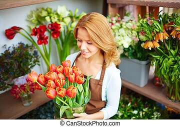 Attractive florist - Young florist carrying vase of red...