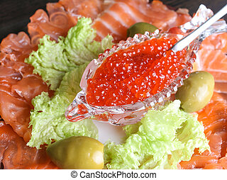 red caviar in a crystal bowl with salmon and green salad -...
