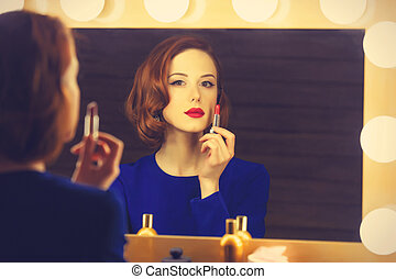 Portrait of a beautiful woman as applying makeup near a...