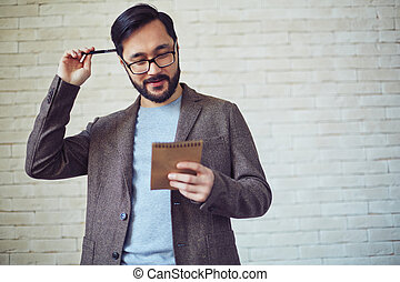 Interesting - Male employee in eyeglasses looking at page of...