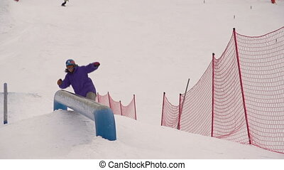 Board Slide - Snowboarder performing board slide...
