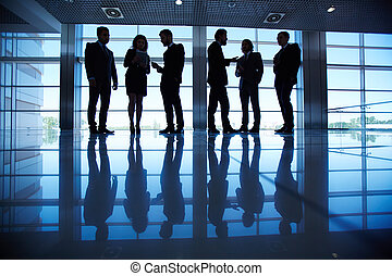 People in the hall - Group of business people communicating...