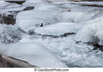 Water stream under ice - Beautiful view of flowing water and...