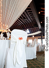 Wedding venue with covered chairs and ceiling decoration - A...