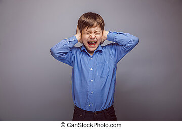 teenager boy covers ears shouting on gray background -...
