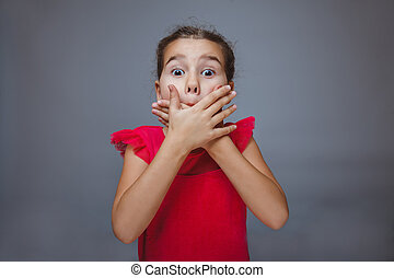 Teen girl child hands covering her mouth feels fright shock...