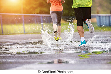 Couple running in rainy weather - Young couple jogging on...