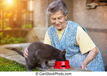 Senior woman with her cat - Senior woman in apron with her...