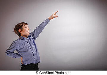 teenager boy shows his hand up on gray background - teenager...