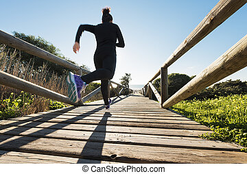 Woman running - Horizontal photo of a young woman running on...