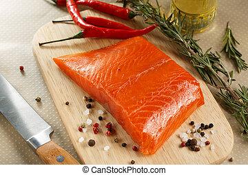 Salmon steak with herbs on cutting board.