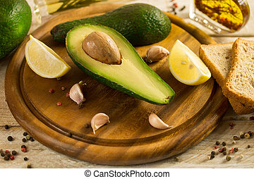 avocado fruit on a cutting board with lemon and garlic