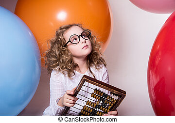 Thoughtful curly teen girl in glasses with wooden abacus on the