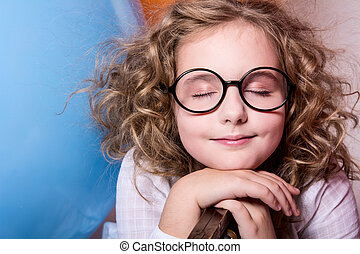 Portrait of teen girl dreaming in glasses with eyes closed...