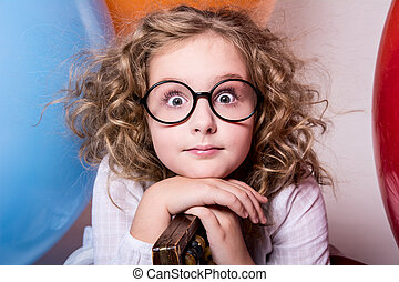 Portrait of surprised curly teen girl in glasses on the...