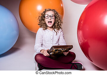 Screaming curly teen girl in glasses with wooden abacus on the b