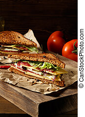 Two pieces of club sandwich on old paper with big cutting...