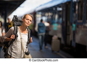 Pretty young woman boarding a trainhaving arrived to her...