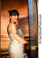 Young woman relaxing in a sauna, taking a break from her...