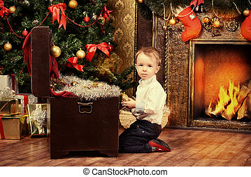 treasure chest - Cute little boy celebrating Christmas at...