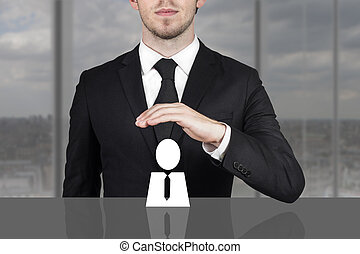 businessman holding protective hand above employee -...