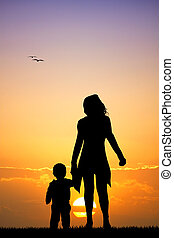 mother and son silhouette at sunset