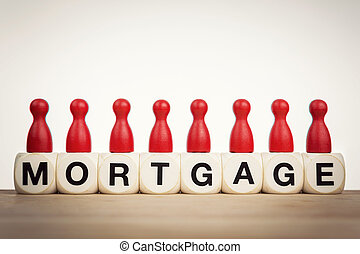 Mortgage concept: Red pawns on the word mortgage spelled by...