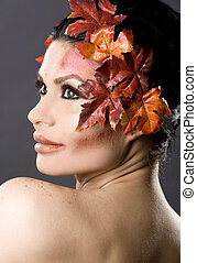 beautiful fall - pretty brunette woman wearing leaves and...