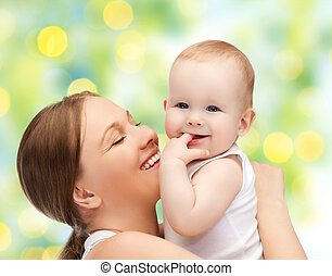 happy mother with baby over green background - people,...