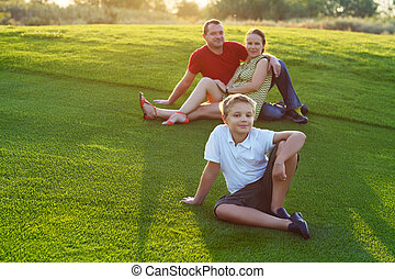 Happy family with son sitting on grass in the park